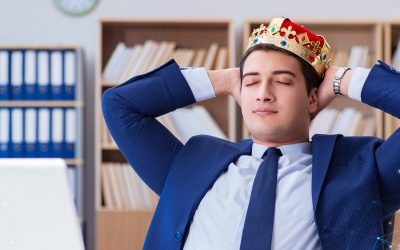 A male employee wearing a crown, professional suit, and resting his hands behind his head