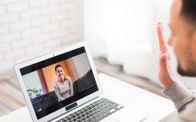 A candidate waving at a recruiter while conducting a video interview