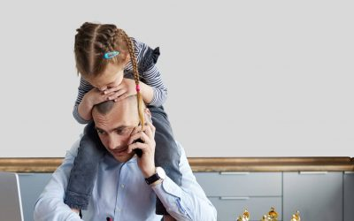 A male recruiter who is trying to conduct a video interview, with his daughter sitting on his shoulder.