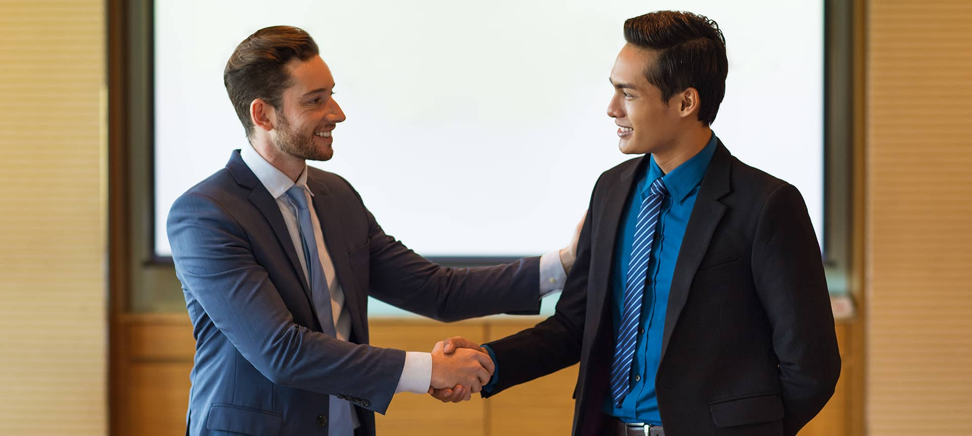 A picture of two male recruiters shaking hands