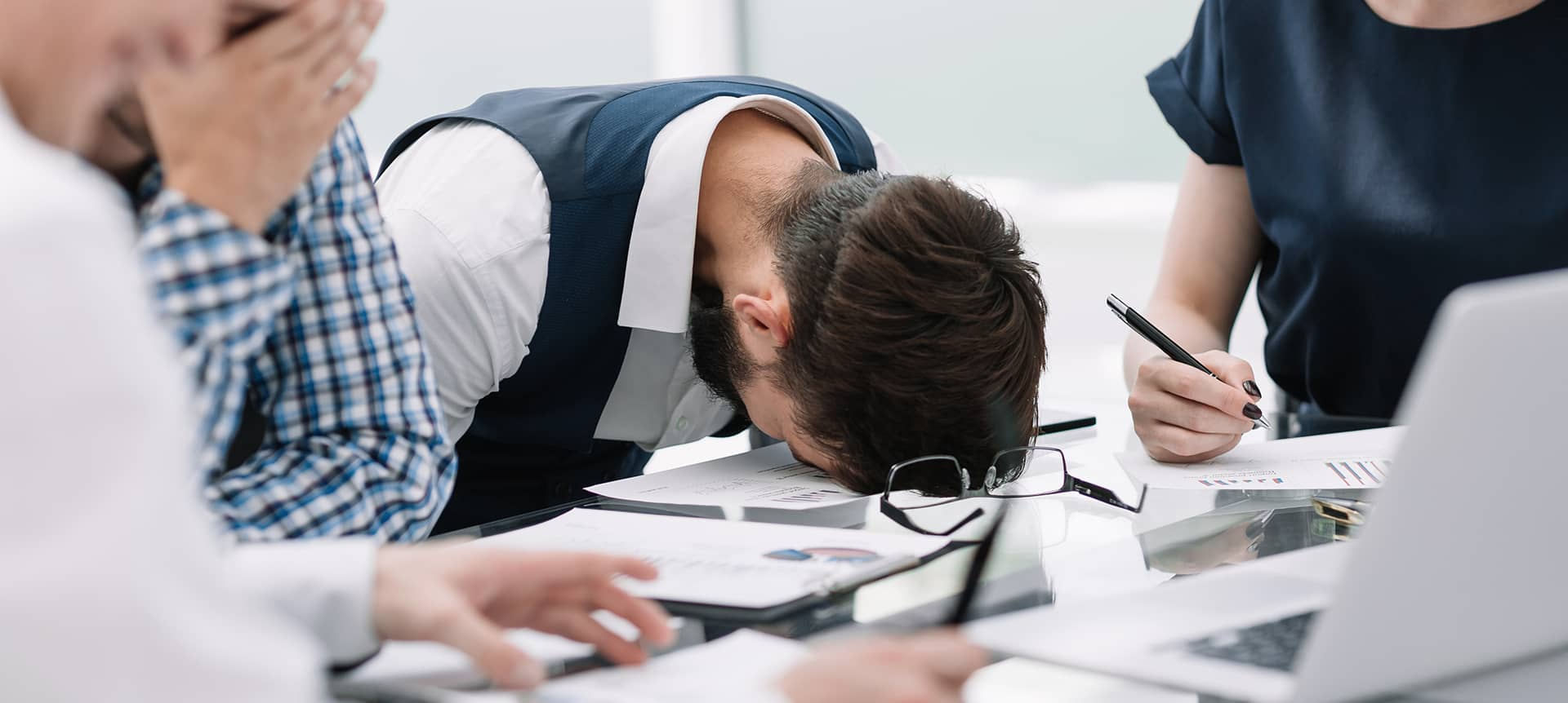 A picture of a made recruiter resting his head on a table, looking disengaged.