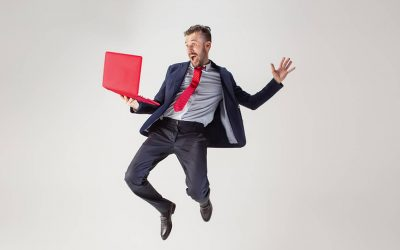 An employee wearing a professional suit, holding a red laptop, and using video assessment interviews to create a winning applicant experience.