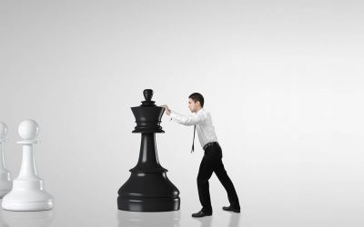 An employee pushing a huge chess piece, symbolizing trying to avoid a failing assessment process.