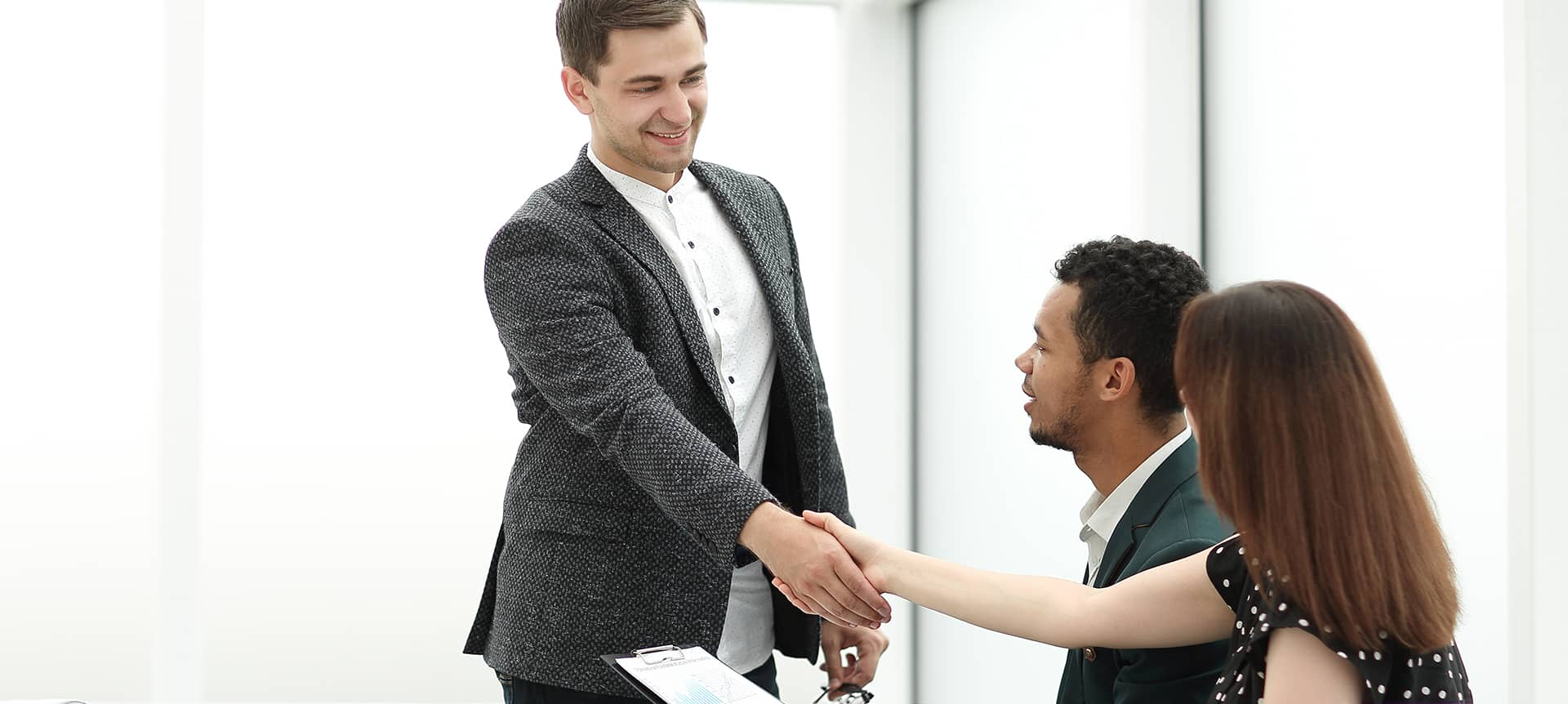 An applicant and HR professional shaking hands.