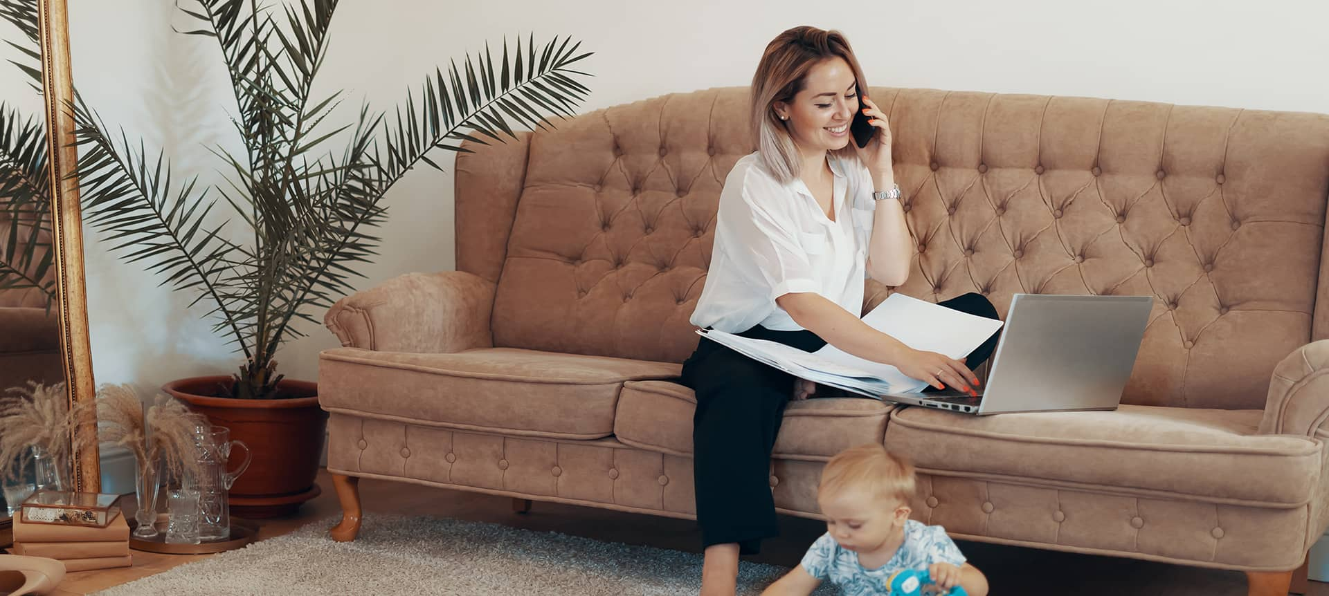 A female employee assessing applicants from home, while sitting on her couch, and looking after her baby.