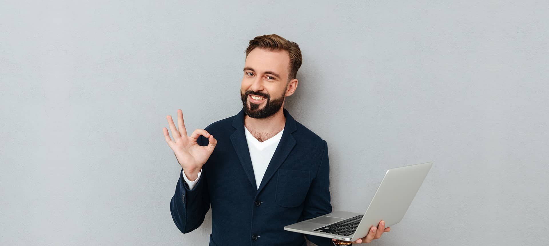 A male employee holding his laptop in one hand and doing an OK gesture with the other hand.