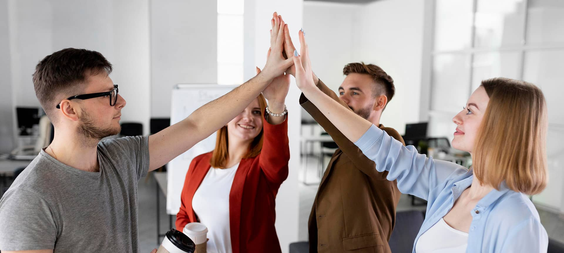 A group of employees high fiving each other