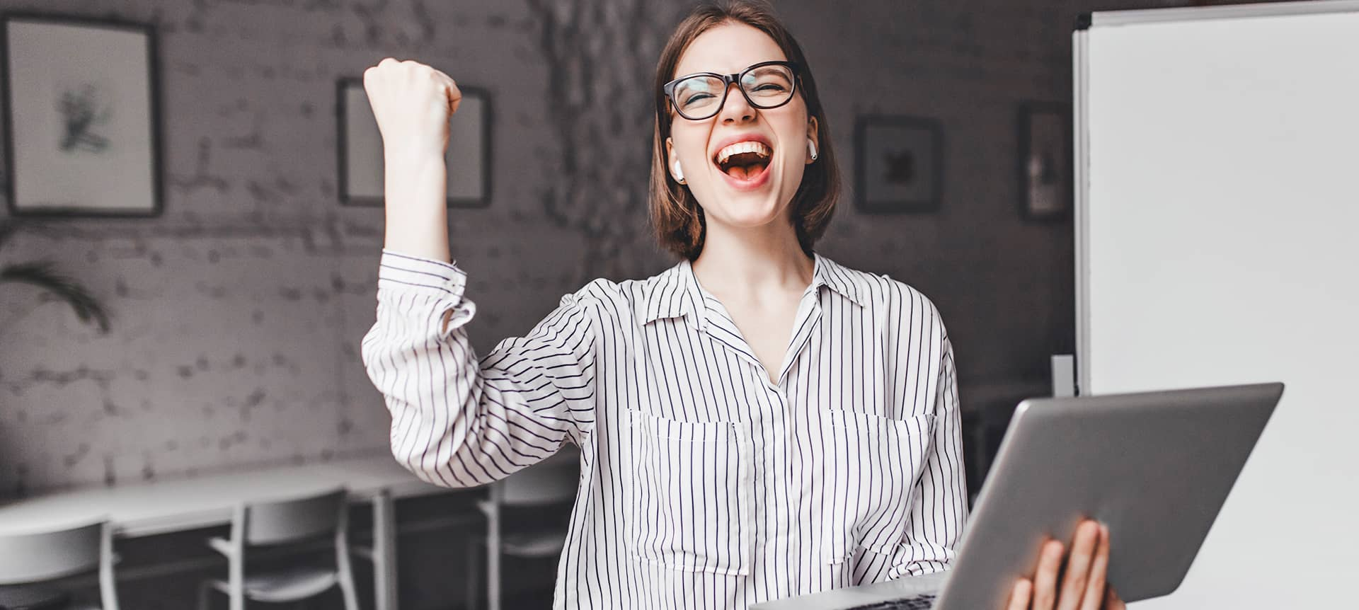A female employee holding her laptop, looking excessively happy, and lifting her palm up in the air.