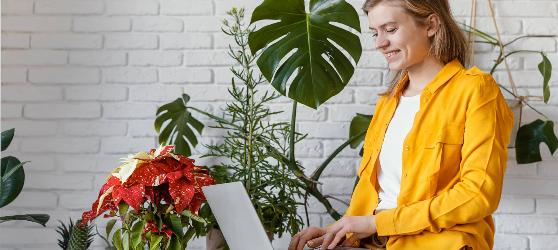 A female employee with blonde hair, wearing a yellow jacket, is working on her laptop.