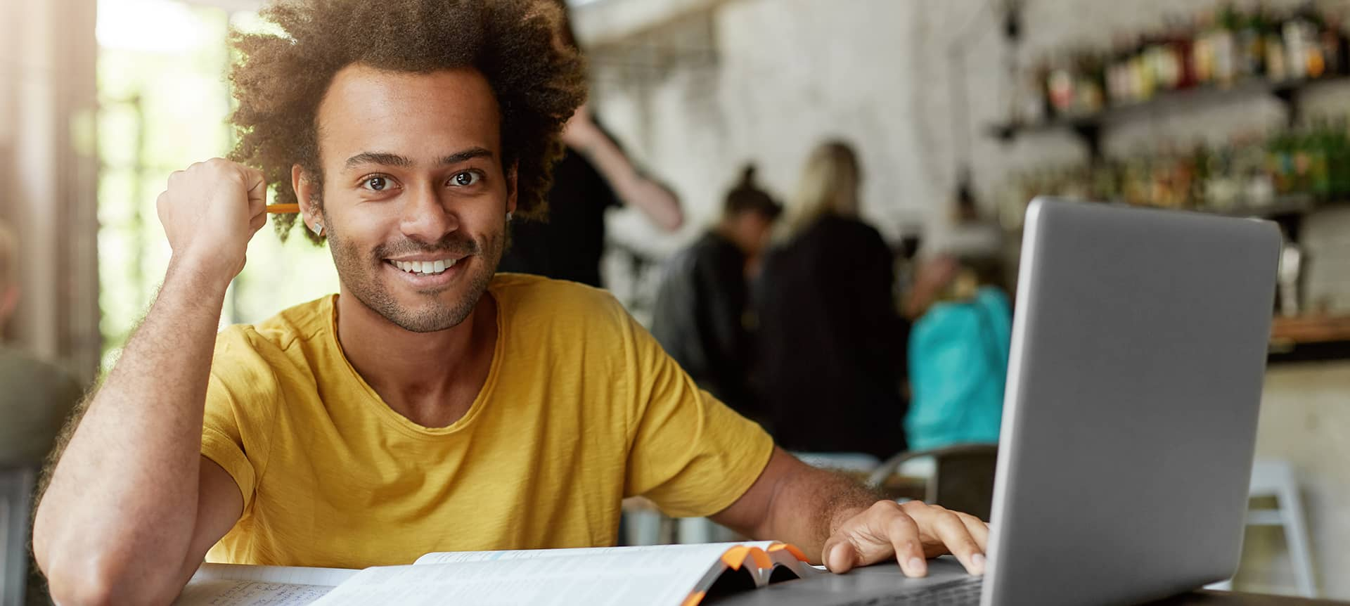 A male applicant, wearing a yellow t-shirt, working on his laptop.