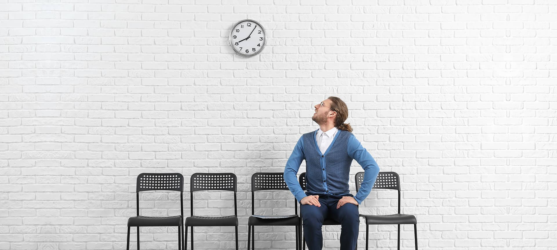 A candidate sitting on a chair and staring at the clock, waiting for his interview to start.