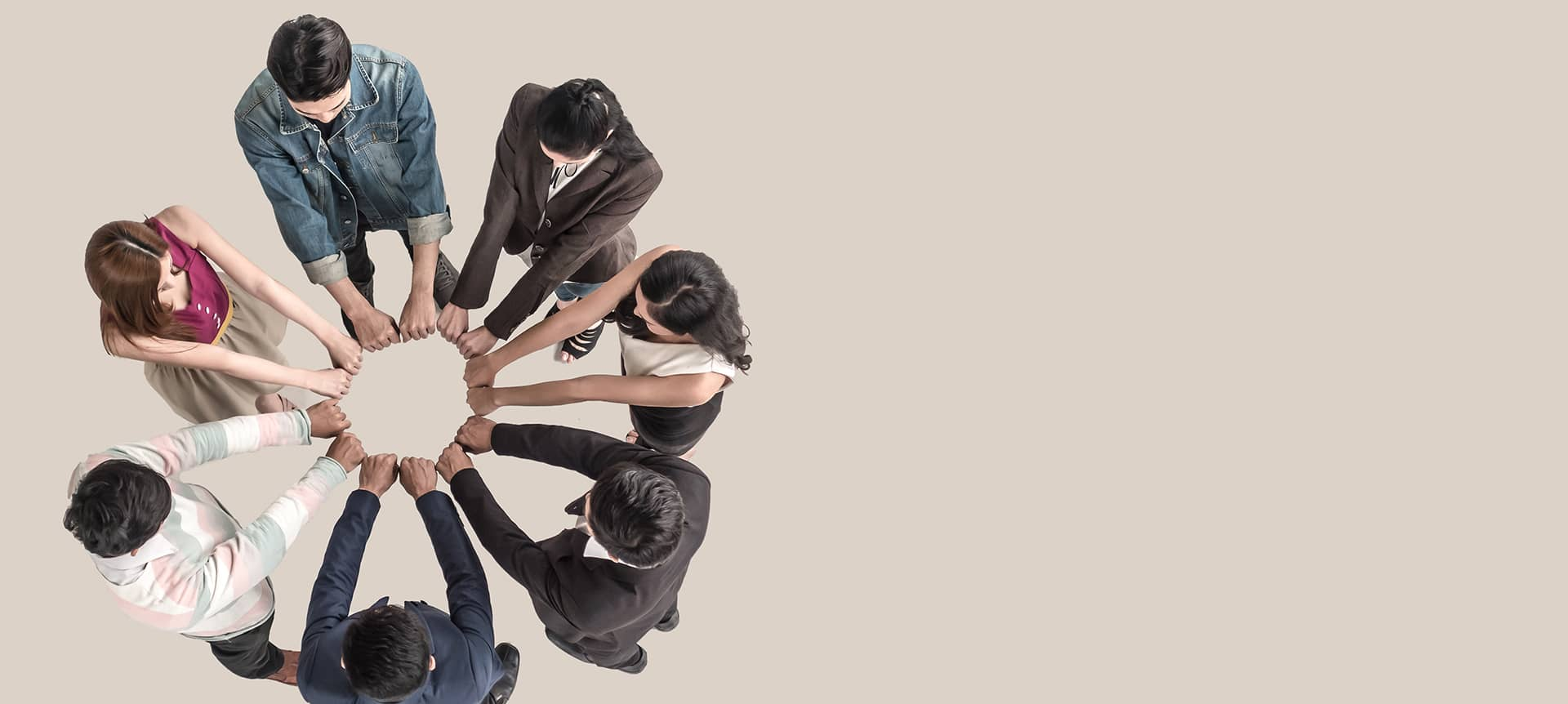 A group of employees huddled around in a circle and extending their arms out to form the shape of a circle.