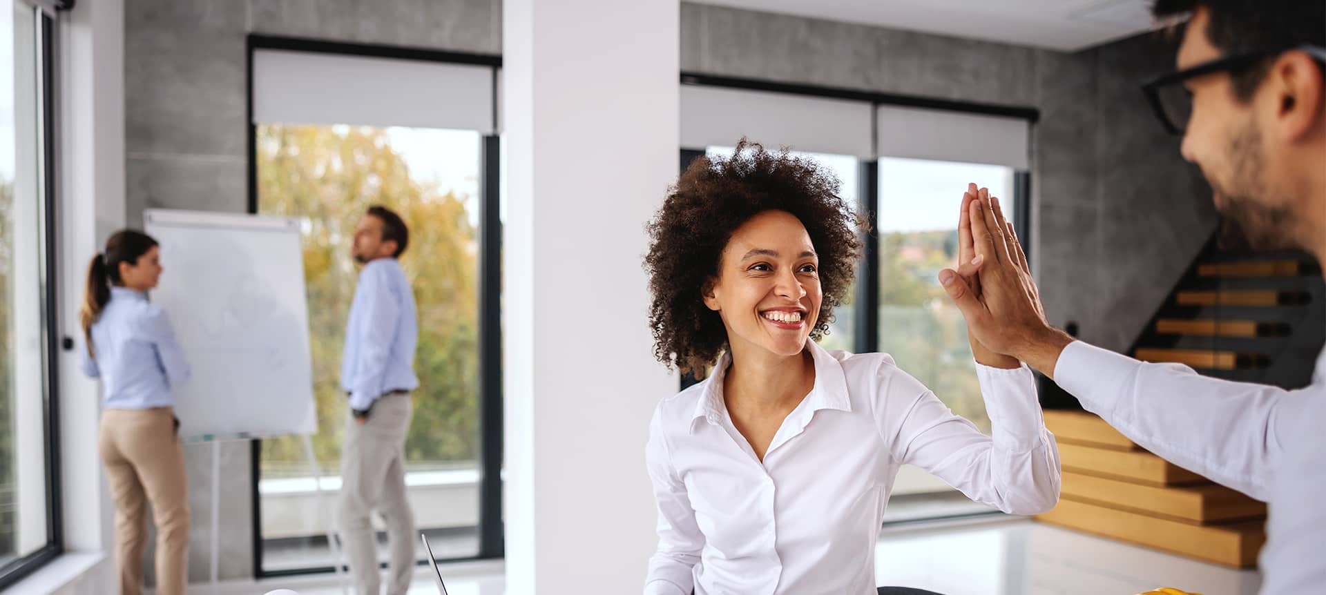 Two employees female and male, high fiving each other at the office.