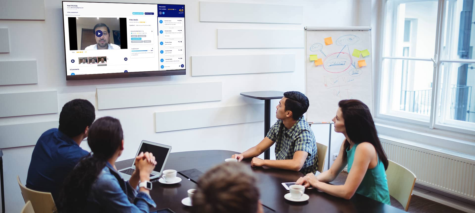 A group of recruiters watching a video assessment interview on TV